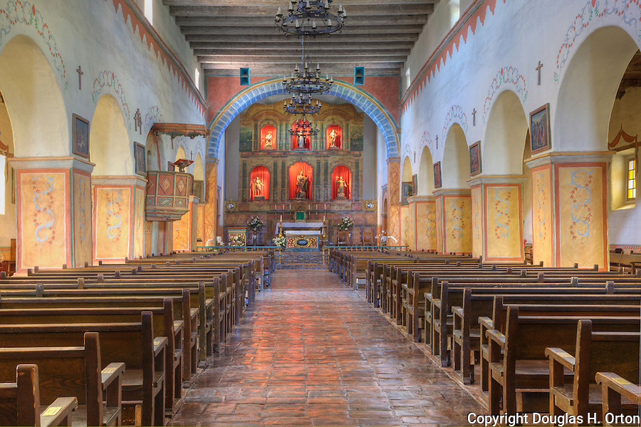 """Chapel Sanctuary with alter, pews, tile floor, adobe building at Mission San Juan Batista, a historic Spanish mission on the """"Mission Trail"""" in the city of San Juan Batista, California.  Founded  1797."""