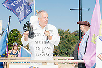 "Harold ""Hal"" Shurtleff, co-founder of New Hampshire conservative summer camp Camp Constitution, wears a hazmat suit decorated with phrases from Orwell's 1984 including ""Ignorance is Strength"" and ""Freedom is Slavery"" as he speaks at a demonstration by the alt-right organization Super Happy Fun America against facemasks, vaccines, and pandemic closures, and in support of the reelection of President Donald J. Trump near the residence of Massachusetts governor Charlie Baker in Swampscott, Massachusetts, on Sat., Sept. 26, 2020. Super Happy Fun America is most well known for organizing the Straight Pride Parade in Boston on August 31, 2019."