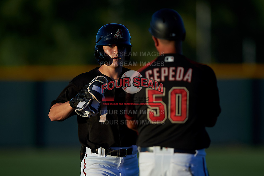 AZL D-backs Corbin Carroll (2) gives his protective equipment to manager Wellington Cepeda (50) after hitting a double in the fourth inning of an Arizona League game against the AZL Mariners on July 3, 2019 at Salt River Fields at Talking Stick in Scottsdale, Arizona. The AZL D-backs defeated the AZL Mariners 3-1. (Zachary Lucy/Four Seam Images)