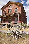 Old old wagon wheel leads the eye to The Hotel Meade, built in mid 1800's, as it stands the test of time at historical Bannack State Park near Dillon MT