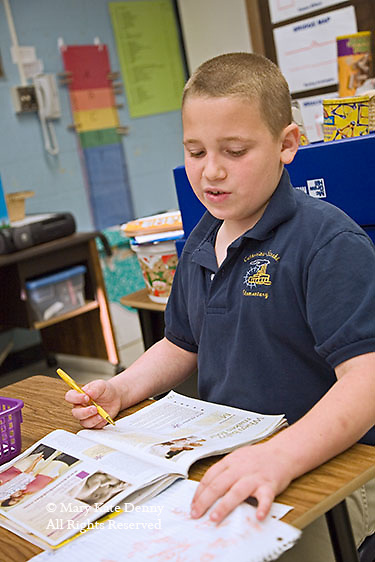 Blonde autistic second grade male works in his book at his desk in school room in.Louisiana