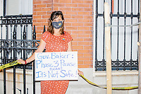 """A demonstrator holds a sign reading """"Gov. Baker: Phase 3 Pause means It's Not Safe"""" as people gathered outside the Massachusetts State House for a protest organized by the Massachusetts Teachers Association against current school reopening plans during the ongoing Coronavirus (COVID-19) global pandemic in Boston, Massachusetts, on Wed., Aug. 19, 2020. The teachers' union, alongside two other Massachusetts teachers' unions, organized the event as part of a mass day of action demanding that the school year starts with remote learning and switch to in-person learning only when health and safety standards can be guaranteed. The sign in the picture refers to the current pause in reopening efforts ordered by Massachusetts governor Charlie Baker after a recent uptick in coronavirus infections."""