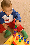 Toddler boy 18 months old playing with colored plastic stacking peg making tower