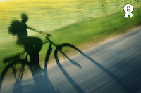 Shadow of cyclist on road and grass (blurred motion) (Licence this image exclusively with Getty: http://www.gettyimages.com/detail/200339731-001 )