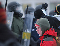 A protester stands in front of riot police as students demonstrate against tuition hikes Thursday, March 1, 2012 at the legislature in Quebec City. Protestors use fresh snow to calm the effects of tear gas.<br /> <br /> PHOTO :  Francis Vachon - Agence Quebec Presse