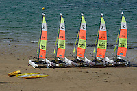 Five catamarans and some kayaks parked on the beach, Brittany, France.