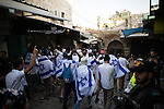 © Joel Goodman - 07973 332324 . 05/06/2016 . Jerusalem , Israel . Thousands of Jews with flags process through the Old City's Muslim district , on the way to the Western Wall , separated from residents of the Old City's Muslim district by Israeli soldiers . Israeli Jews celebrate Jerusalem Day . Photo credit : Joel Goodman