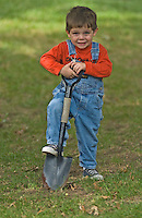 boy in blue jean overalls and red shirt with shovel and sneakers