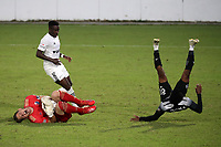 RICHMOND, VA - SEPTEMBER 30: Serge Ngoma #81 of New York Red Bulls II is sent tumbling after a collision with Alex Tambakis #1 of North Carolina FC while challenging for the ball during a game between North Carolina FC and New York Red Bulls II at City Stadium on September 30, 2020 in Richmond, Virginia.