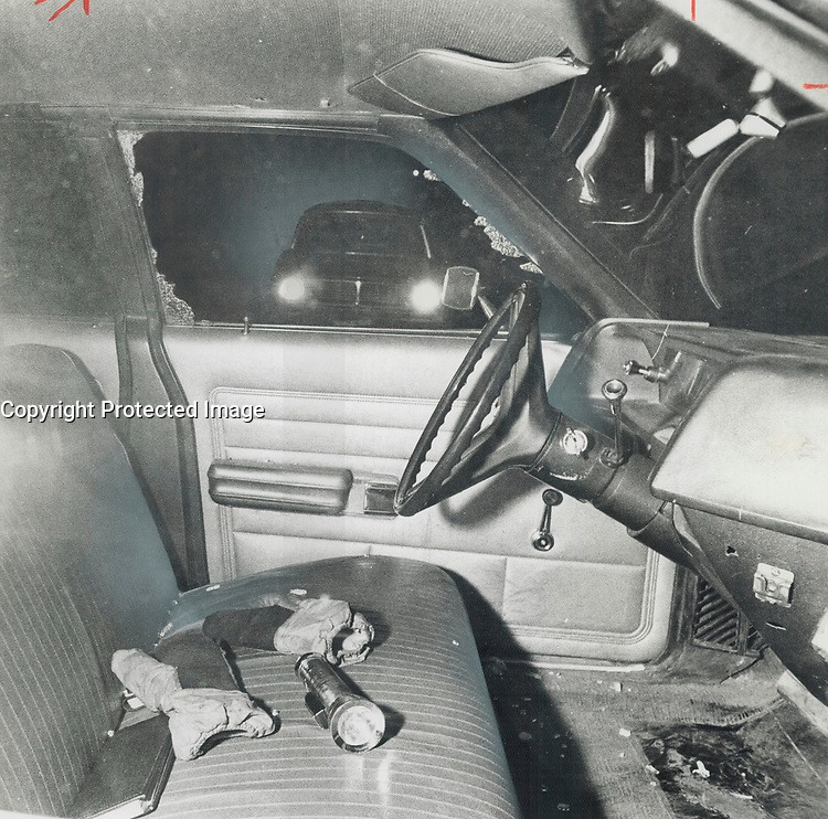 In the cruiser driven by Constable James Lothian; his gloves; flashlight and book of traffic tickets lie on the front seat after he was shot. Police do not know when or how the front window on the driver's side of the car was shattered.