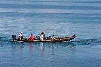 Zanzibar, Tanzania.  Canoe and Passengers being Towed into Port, Stone Town.