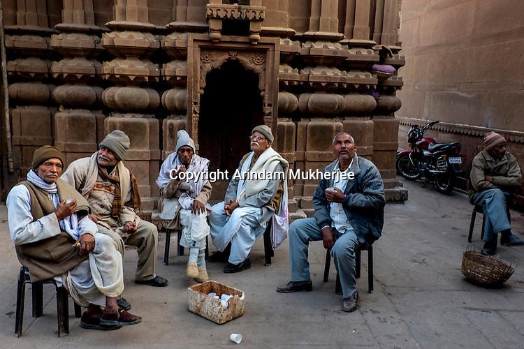 Indan old men drinks tea in front of a temple in Varanasi, Uttar Pradesh, India.