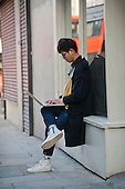 A young man uses a laptop in the street in Shoreditch, London, a run-down commercial district  also known as Silicon Roundabout, which is undergoing gentrification as it becomes a centre for web-based companies and IT start-ups.