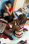 Education preschool 4 year olds two girls playing pretend play game together, one talking on phone, the other using a stack of magent blocks, talking