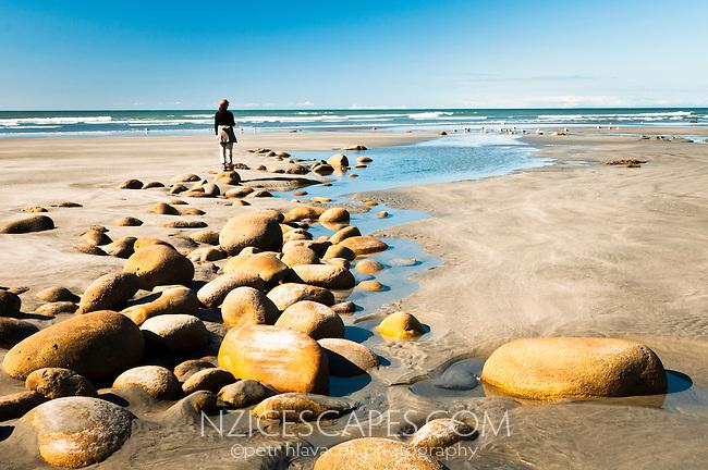 A woman walking on Carters Beach in Westport - Buller Region, Central West Coast, New Zealand
