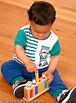 11 month old baby boy sitting on floor playing with toy using pincer grip to play with peg toy Hispanic vertical