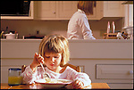 young girl eating breakfast cereal at home