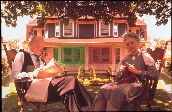 elder couple relaxing on lawn in rocking chairs