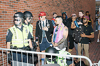 """Alt-right provocateur Milo Yiannopoulos stands behind barricades with police away from counter-protesters after marching in the Straight Pride Parade in Boston, Massachusetts, on Sat., August 31, 2019. Yiannopoulos wore a sequined red hat in the style of Make America Great Again (MAGA) hats reading """"Make America Straight Again."""" Yiannopoulos addressed the crowd with a short speech on arrival and then rode the """"Trump Unity Bridge"""" float for the duration of the parade. Despite leading the Straight Pride Parade and singing along with patriotic American songs throughout the parade, Yiannopoulos is gay and is not an American citizen."""