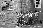 Primary school playground. Boys playing together. South London. 1970s   Multiracial multi ethnic black and white children having fun play time at school 70s UK