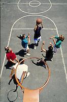 TEEN FRIENDS PLAYING BASKETBALL IN SCHOOLYARD. HIGH SCHOOL TEENS. OAKLAND CALIFORNIA USA.