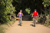 Attractive couple riding bikes on the Zilker Park Hike And Bike Trail in Austin, Texas.
