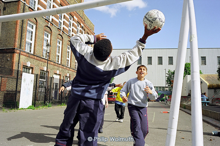 Goalkeeper makes a save during a game of football at Ashburnham Adventure Playground in World's End, Chelsea.