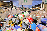 A recycling bin holds various empty tin cans.