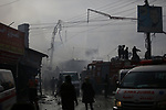 Palestinians put out a fire that broke out in a market in the refugee camp of Nuseirat in central Gaza Strip, on March 5, 2020. Photo by Osama Baba