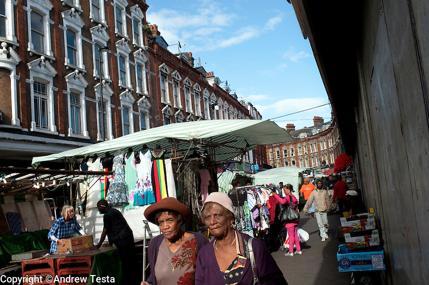 UK. London. 15th July 2010.Shoppers walk through market stalls on Electric Avenue in Brixton..©Andrew Testa for the New York Times