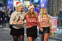 Pictured: Three women in festive jumpers walk down Wind Street, Swansea, south Wales, UK. Friday 21 December 2018<br /> Re: Black Eye Friday, also known as Mad Friday or Black Friday which is the last Friday before Christmas Day.