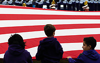 Young Husky fans help the Husky Band hold the American flag during the national anthem.
