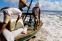 A Brazilian fisherman (jangadeiro) cuts ice blocks loaded on the boat on the beach of Prainha, Ceará state, northeastern Brazil, 8 March 2004. Jangadeiros, working on a unique wooden raft boat called jangada, keep the tradition of artisan fishing for more than four hundred years. However, being a fisherman on jangada is highly dangerous job. Jangadeiros spend up to several days on high-sea, sailing tens of kilometres far from the coast, with no navigation on board. In the last two decades jangadeiros have been facing up the pressure from motorized vessels which use modern, effective (and environmentally destructive) fishing methods. Every time jangadeiros come back from the sea with less fish.