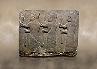 Photo of Hittite monumental relief sculpted orthostat stone panel of a Procession. Basalt, Karkamıs, (Kargamıs), Carchemish (Karkemish), 900-700 B.C.  Marching female figures. Anatolian Civilisations Museum, Ankara, Turkey.<br /> <br /> It is a depiction of three marching female figures in long dress with a high headdress at their head. These women are considered to be the nuns of the Goddess Kubaba. They have a bunch of Spica in their right hand, and objects similar to a sceptre in their left hand. <br /> <br /> Against a brown art background.