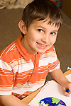 Education elementary Kindergarten art activity drawing with markers portrait of boy smiling closeup looking up from his drawing of the earth vertical