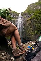 Young woman in green jacket and brown hiking skirt, enjoying the view of Hanakapiai Falls, Napali Coast, Kauai, Hawaii