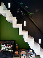 A simple concrete stairway leads from the kitchen up to the sleeping loft, lit by built-in wall lights
