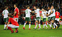 Jeff Hendrick of Ireland (13) and team mate Shane Duffy (C) celebrate their win while Sam Vokes of Wales (L) sits on the ground dejected during the FIFA World Cup Qualifier Group D match between Wales and Republic of Ireland at The Cardiff City Stadium, Wales, UK. Monday 09 October 2017
