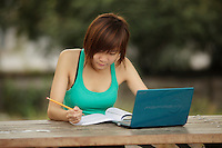 August 2012 - Montreal (Qc) CANADA - MODEL RELEASE photo of a 19 year old asian (Vietnamese) female teen <br /> using a notebook  to do her homework in Montreal Old Port