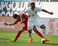 CHARLOTTE, NC - JUNE 23: Roberney Caballero #22 defends against Derek Cornelius #4 during a game between Cuba and Canada at Bank of America Stadium on June 23, 2019 in Charlotte, North Carolina.