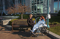 Woman and pregnant older child in wheelchair with IV bags and monitoring equipment sit outside hospital on winter day
