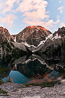 Scenic view of Dragontail Peak with alpenglow reflected in Colchuck Lake, Alpine Lakes Wilderness, WA.