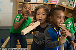 Preschool 4 year olds group of three boys pretending to sing holding wooden blocks as microphones