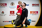 © Joel Goodman - 07973 332324 . 15/10/2017 . Manchester , UK . A man who ran the race poses with his son on the winners' podium . Friends and families wait for athletes at the finish line in the Greater Manchester Half Marathon in Old Trafford . Photo credit : Joel Goodman
