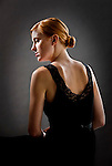 Young red haired woman wearing black dress with back to camera