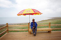 A local man on 'Bird Island', a famous tourist spot at Qinghai Lake. Qinghai Lake, China's largest inland body of water lies at over 3000m on the Qinghai-Tibetan Plateau. The lake has been shrinking in recent decades, as a result of increased water-usage for local agriculture. Qinghai Province. China. 2010