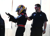 Feb 3, 2016; Chandler, AZ, USA; NHRA top fuel driver J.R. Todd is helped with safety gear by a crew member during pre season testing at Wild Horse Pass Motorsports Park. Mandatory Credit: Mark J. Rebilas-USA TODAY Sports