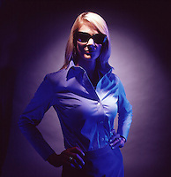 Dramatically lit photograph of blond woman with dark sunglasses