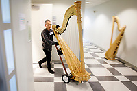 Lyon and Healy Technician John Papadolias moves a harp from a practice room to the stage during Stage III at the 11th USA International Harp Competition at Indiana University in Bloomington, Indiana on Wednesday, July 10, 2019. (Photo by James Brosher)