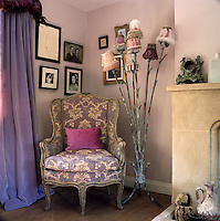 A standard lamp with a myriad small shades is placed next to a giltwood armchair upholstered in violet brocade